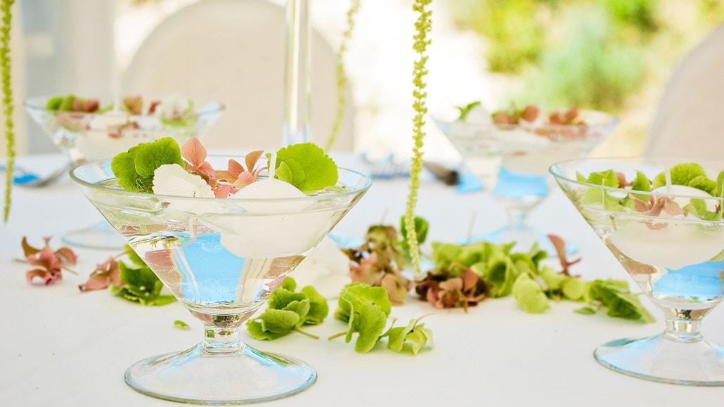 Žaliais žiedlapiais papuoštas vestuvių stalas